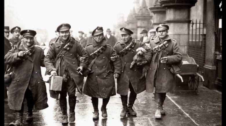 five WWI soldiers laughing, one carrying puppy