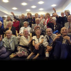large group of old people happily cheer Sir Nicholas Winton